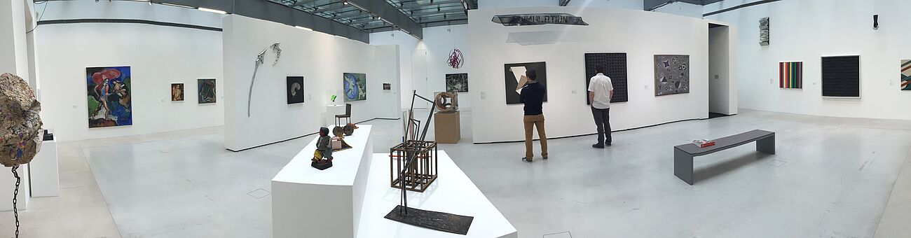 picture of an art exhibition, white room, two men staying in front of artworks